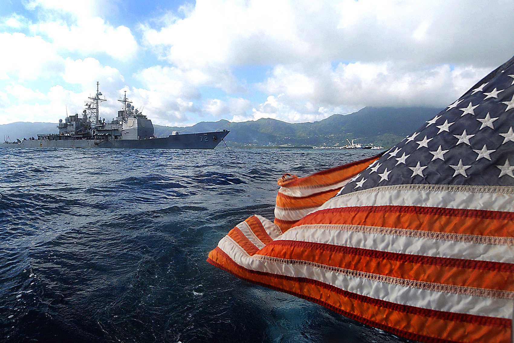 american-flag-flying-behind-a-navy-ship-in-the-ocean-stock-photography.jpg